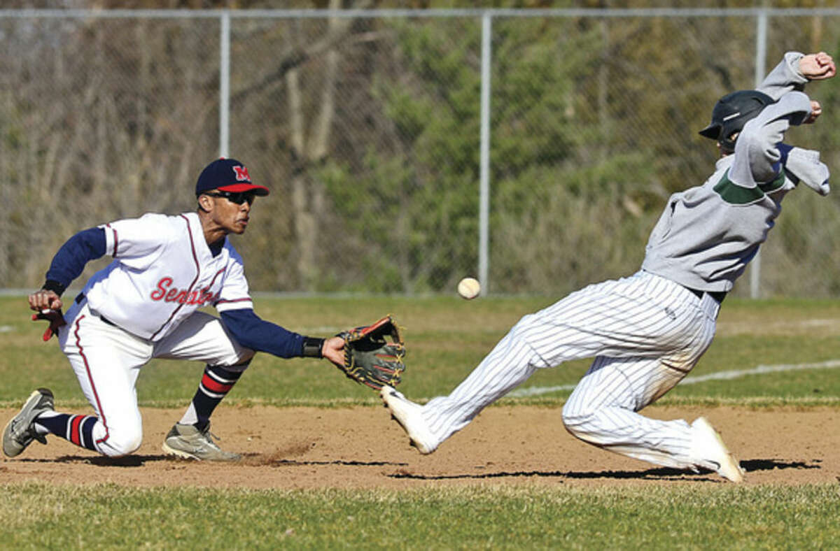 Hour photo/Erik Trautmann Brien McMahon second baseman Edwin Owolo, left, tries to get a tag on Norwalk High's Mike Gonzalez in Saturday's intra-city baseball game at Brien McMahon.