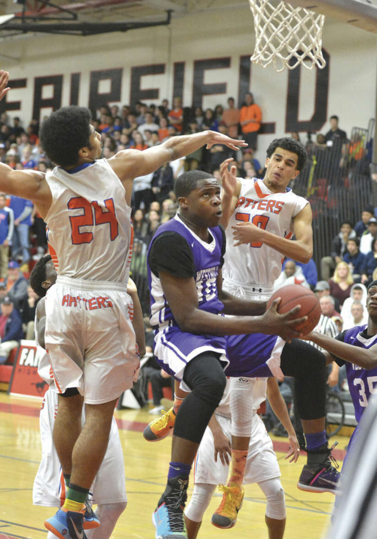 Westhill's Tyrell Alexander tries to put up a shot between two Danbury defenders during Thursday's game.