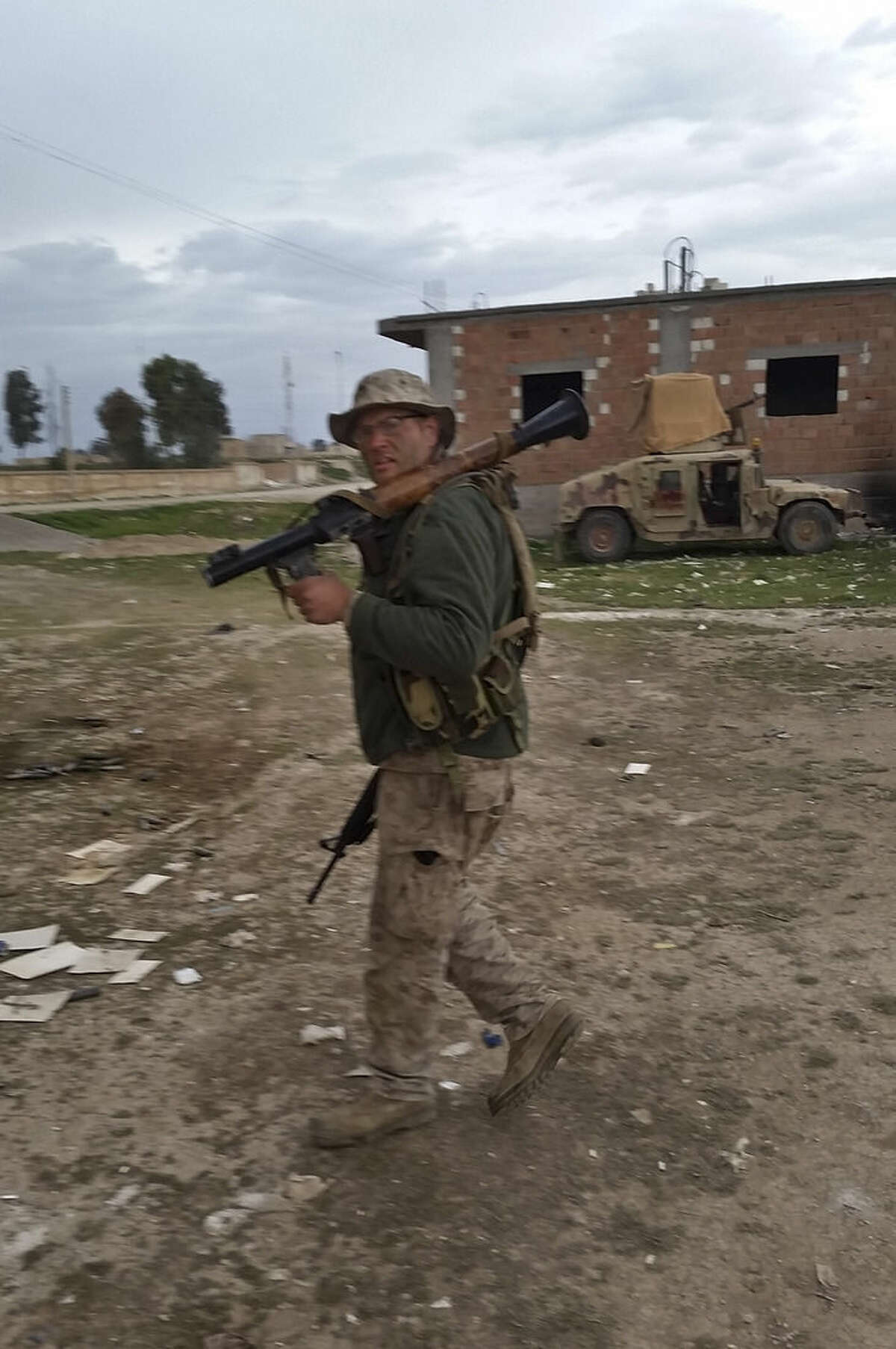 In this March 12, 2015 photo Jamie Lane, 29, an American veteran originally from Mt. Pleasant Michigan, carries a rocket-propelled grenade during fighting alongside Kurdish militiamen against Islamic State militants in Tel Tamr, Syria. Lane is among growing number of Iraq war veterans returning to the battlefield, this time without the American military, to join in the fight against the Sunni militants who now hold territory in a third of Iraq and Syria. (Courtesy Jamie Lane via AP)