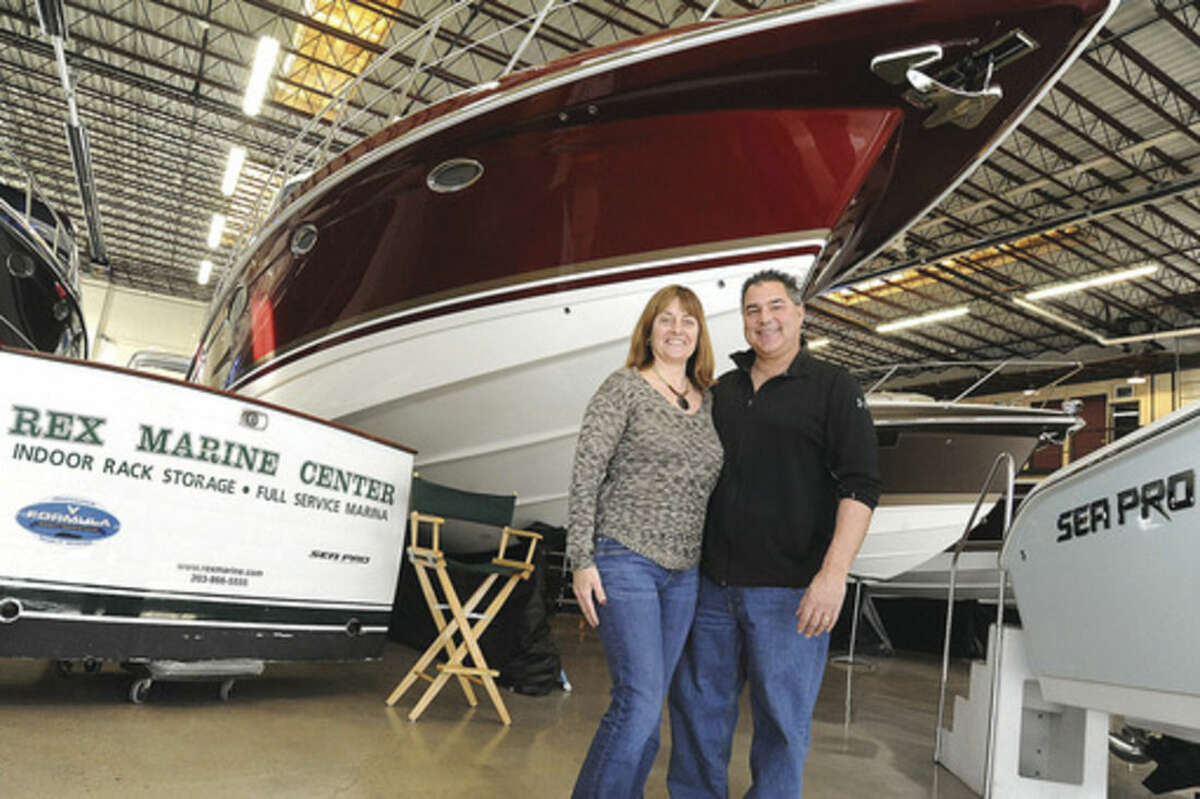 @Hour Blue=[C] Hour photo/Matthew Vinci Paul and Rochelle Aballo in front of their custom-built 45 Formula boat on the showroom floor at Rex Marine in Norwalk Sunday. Rex Marine celebrated its 80th anniversary.