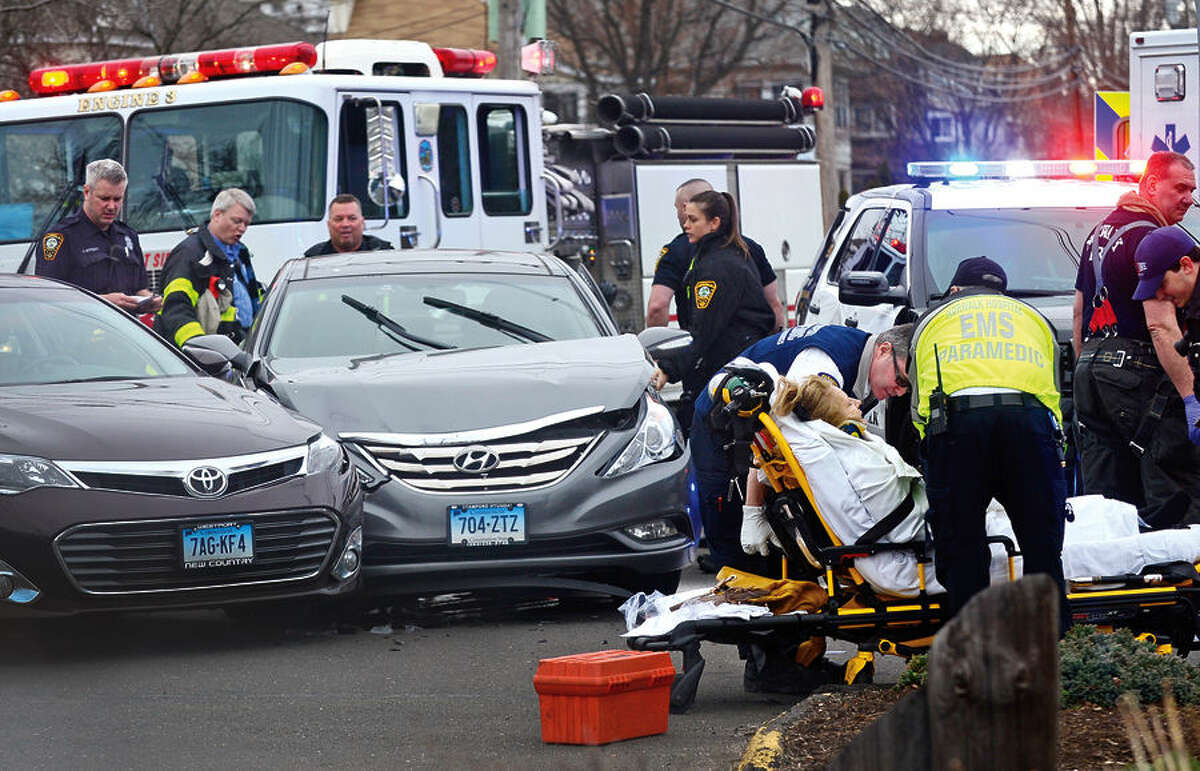 Hour photo / Erik Trautmann Norwalk emergency personnel tend to an injured woman after a two car accident on Gregory Boulevard Tuesday morning.