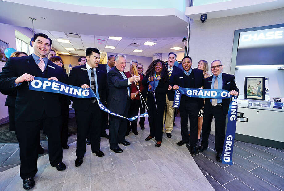 Hour photo / Erik Trautmann Chase Bank employees Kevin Smith, Victor Cuba, Salvatore Salta and Edward Berdomo help Norwalk Mayor Harry Rilling and Branch Manager Audrey Mlllagayamova, center, cut the ribbon for the grand opening of the new Chase Bank Tuesday in the West Ave Waypointe development.