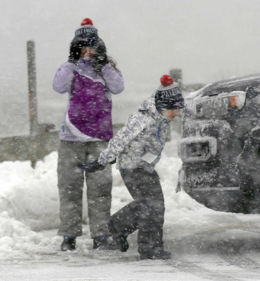Carly, left, , and Matthew Steenstra of Barnstable, mass., brace against the wind and snow at Millway Beach during high tide Monday, Feb. 8, 2016. A wind-driven winter storm brought blizzard conditions to Cape Cod and threatened to drop up to 18 inches of snow on southeastern Massachusetts on Monday. (Ron Schloerb/The Cape Cod Times via AP)