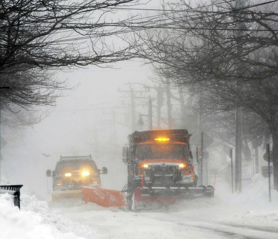 Plows move snow off Main street in Hyannis, Mass., Monday, Feb. 8, 2016. A wind-driven winter storm brought blizzard conditions to Cape Cod and threatened to drop up to 18 inches of snow on southeastern Massachusetts on Monday. (Ron Schloerb/The Cape Cod Times via AP)