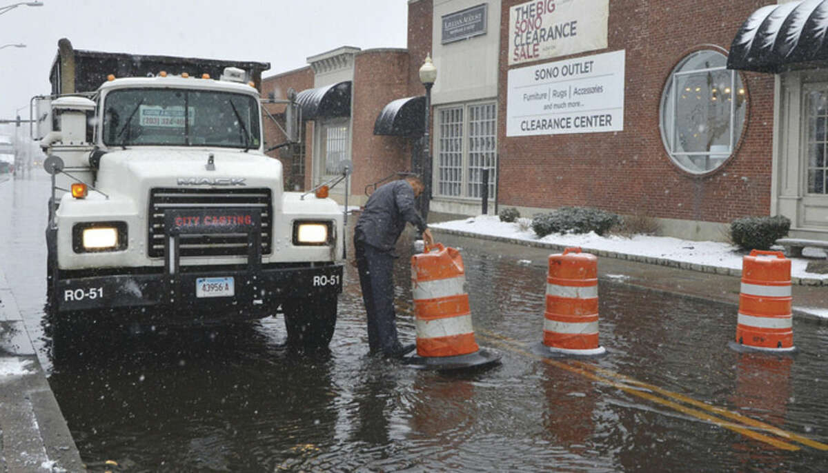 Hour Photo/Alex von Kleydorff A City Carting truck driver moves a DPW barrel to get his truck through a flooded Water St