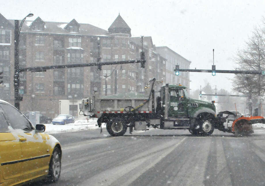 Hour photo/Matthew VinciA Norwalk Department of Public Works plow cuts across West Avenue in Norwalk Monday afternoon clearing the way as snow began to accumulate across the city.