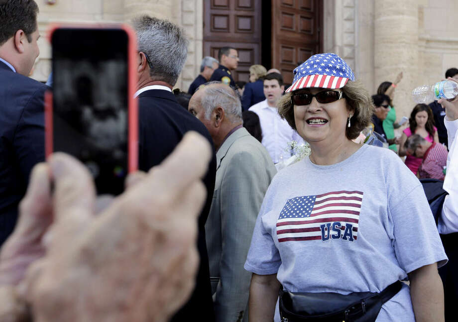 Barbara Rodriguez, of Miami, poses for a photograph outside of the Freedom Tower where Sen. Marco Rubio, R-Fla., is launching his Republican presidential campaign, Monday, April 13, 2015, in Miami. Rodriguez arrived in the U.S. from Cuba 49 years ago, and had her immigration papers processed in the Freedom Tower. (AP Photo/Lynne Sladky)
