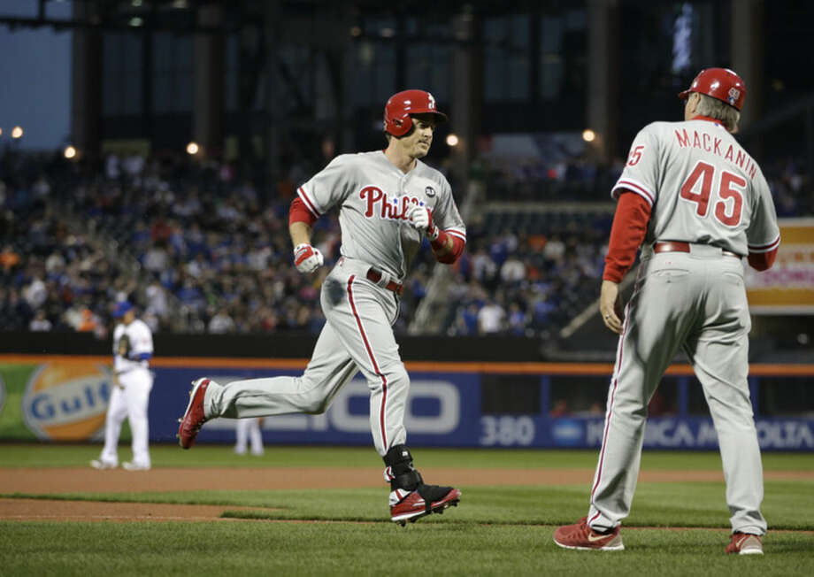 Philadelphia Phillies' Chase Utley passes third base coach Pete Mackanin (45) on the way home after hitting a first-inning solo home run off New York Mets starting pitcher Matt Harvey in a baseball game in New York, Tuesday, April 14, 2015. (AP Photo/Kathy Willens)