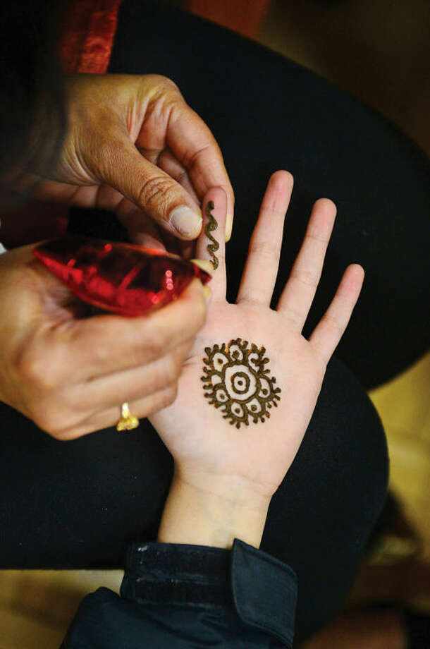 Hour photo / Erik Trautmann Visitors had their hands painted with Henna during an Indian Spring Festival at the Wilton Family YMCA Saturday afternoon.