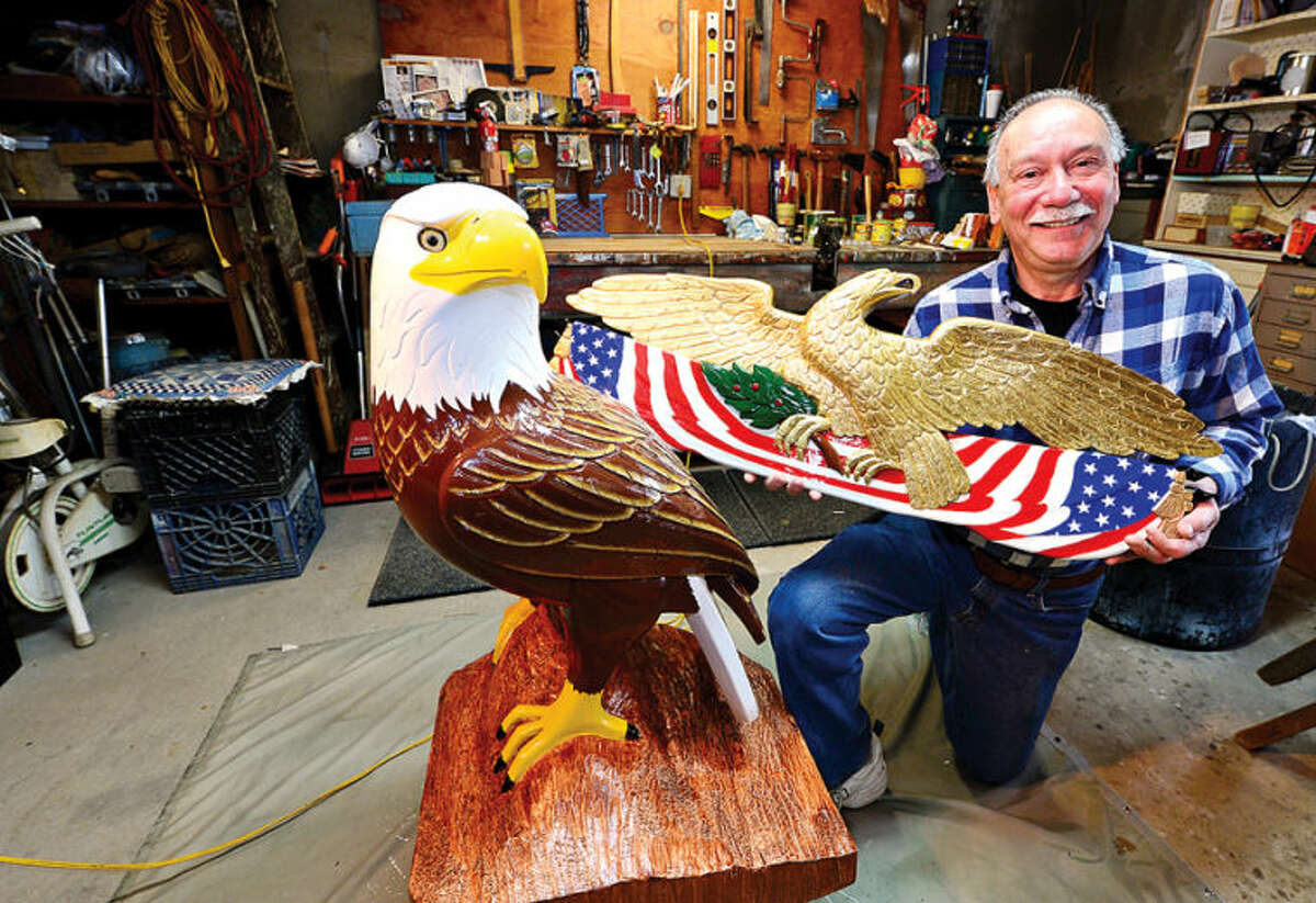 Hour photo / Erik Trautmann Longtime Norwalk resident Mike Caputo, a retired auto body worker, recently took up woodworking and carved a 3-foot eagle out of a 300 pound block of wood.