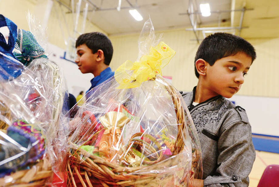 Hour photo / Erik Trautmann Hirsh Iyre, 6, sells raffle tickets during an Indian Spring Festival at the Wilton Family YMCA Saturday afternoon.