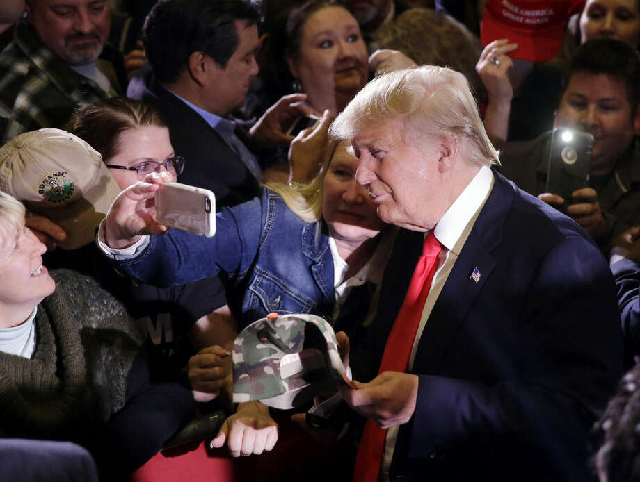 Republican presidential candidate Donald Trump takes pictures with supporters during a rally Tuesday, Feb. 23, 2016, in Reno, Nev. (AP Photo/Marcio Jose Sanchez)