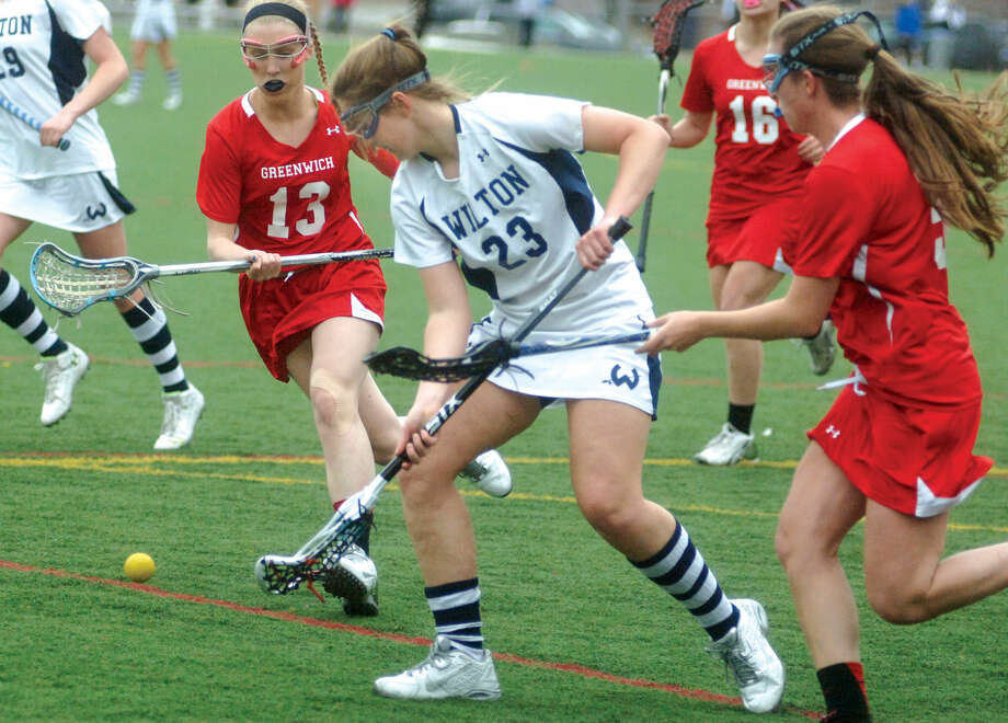 Wilton's Sara Dickinson tries to pick up a ground ball as Greenwich's Caitlin Brady (13) and Megan Collins (9) swarm to play defense. (Hour photo/Matthew Vinci)