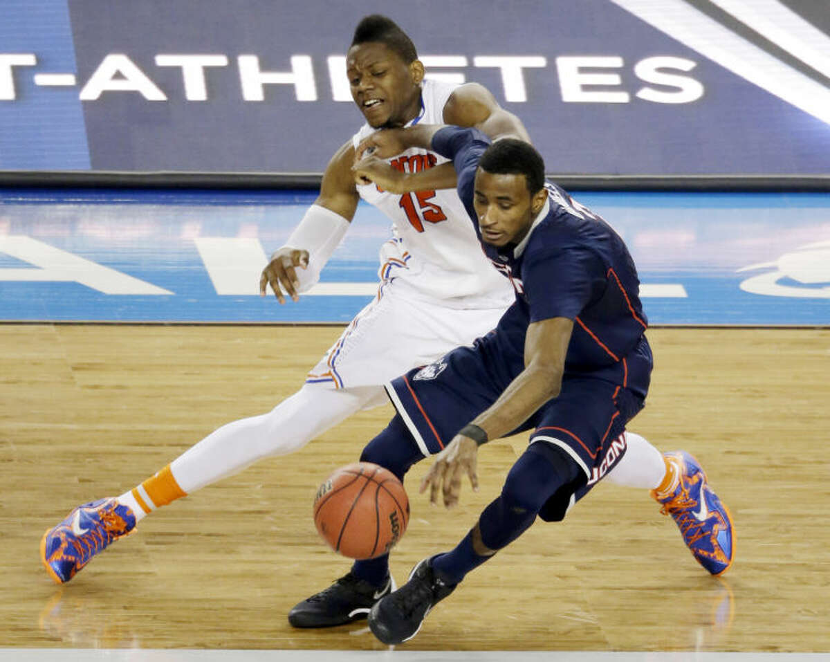 Connecticut forward DeAndre Daniels works to maintain control of the ball as Florida forward Will Yeguete (15) defends during the second half of the NCAA Final Four tournament college basketball semifinal game Saturday, April 5, 2014, in Arlington, Texas. (AP Photo/Tony Gutierrez)