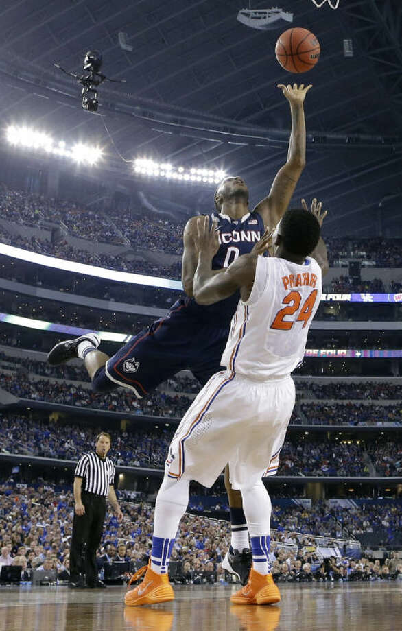 Connecticut forward Phillip Nolan, left, shoots over Florida forward Casey Prather during the second half of an NCAA Final Four tournament college basketball semifinal game Saturday, April 5, 2014, in Arlington, Texas. (AP Photo/Eric Gay)