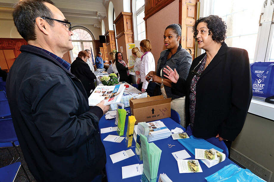 Hour photo / Erik Trautmann Local resident Vasil Raev chats with Marie Laurette Gachenlin and Lisa Alhabal of the Southwestern CT Agency on Aging during Senior Citizens' Connection Day where seniors garnered information on cost-savings opportunities including tax relief offered Wednesday in Community Room at Norwalk City Hall.