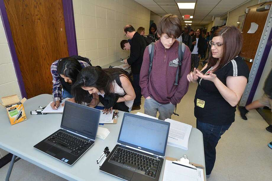 Westhill High School junior Liam Bannon checks in with Elana Mitchell with the College Board as students and teachers and administrators turn out for an open casting call to be included in the 2015-2016 College Board brochures.
