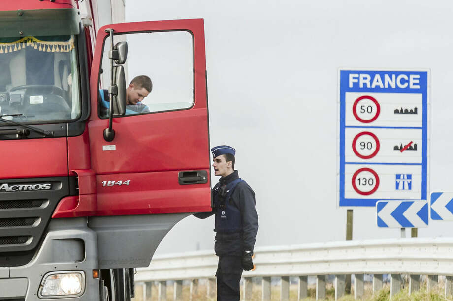 A policeman patrols a truck, on the French-Belgian border in Adinkerke, Belgium, on Wednesday, Feb. 24, 2016. Belgium is reinforcing its borders with France close to the Calais to avoid a flood of people crossing the border if the French migrant camp gets closed. (AP Photo/Geert Vanden Wijngaert)