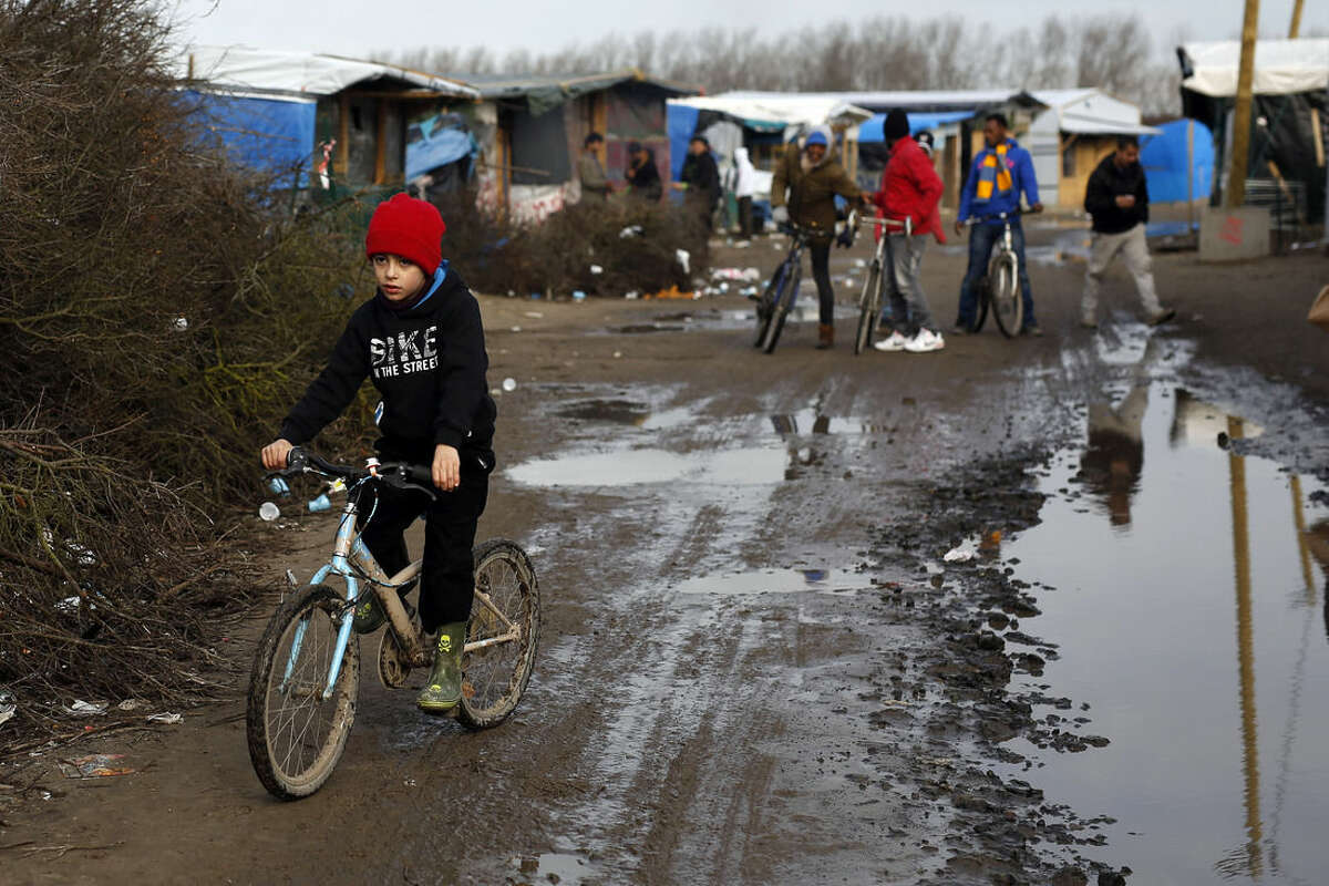"""AP Photo/Jerome Delay A child rides his bicycle in a makeshift camp for migrants near Calais, France, Thursday Feb. 25, 2016. The clock is ticking for some hundreds of migrants waiting for a judge to decide whether to postpone an eviction order in the camp locally referred to as """"jungle."""""""