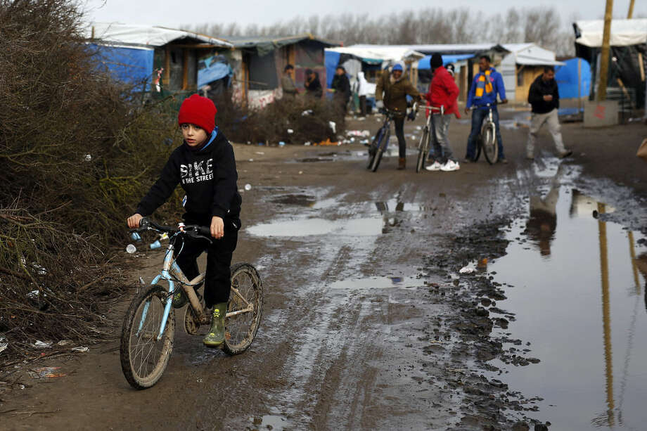 """AP Photo/Jerome DelayA child rides his bicycle in a makeshift camp for migrants near Calais, France, Thursday Feb. 25, 2016. The clock is ticking for some hundreds of migrants waiting for a judge to decide whether to postpone an eviction order in the camp locally referred to as """"jungle."""""""