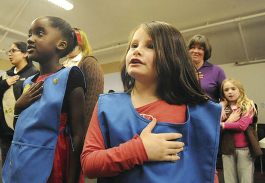 Hour photo/Matthew VinciGirl Scouts Lisa Rangel, 6, and Chloe Gelin, 7, recite the pledge of allegiance Sunday at the South Norwalk Public Library where the Norwalk Girl Scouts celebrated World Thinking Day.