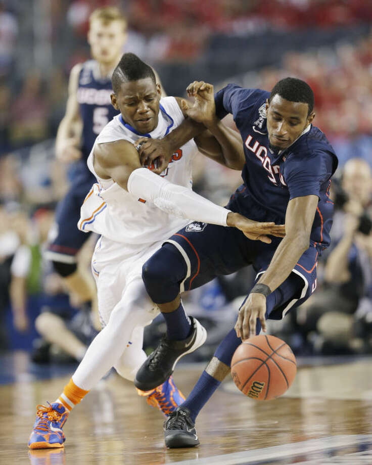 Florida forward Will Yeguete (15) reaches in against Connecticut forward DeAndre Daniels (2) during the second half of the NCAA Final Four tournament college basketball semifinal game Saturday, April 5, 2014, in Arlington, Texas. (AP Photo/David J. Phillip)