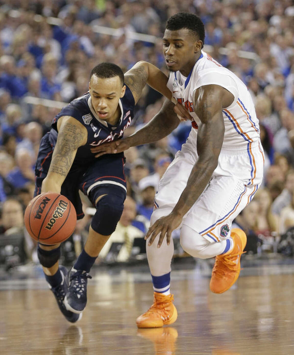 Connecticut guard Shabazz Napier, left, drives past Florida forward Casey Prather during the second half of an NCAA Final Four tournament college basketball semifinal game Saturday, April 5, 2014, in Arlington, Texas. (AP Photo/Eric Gay)