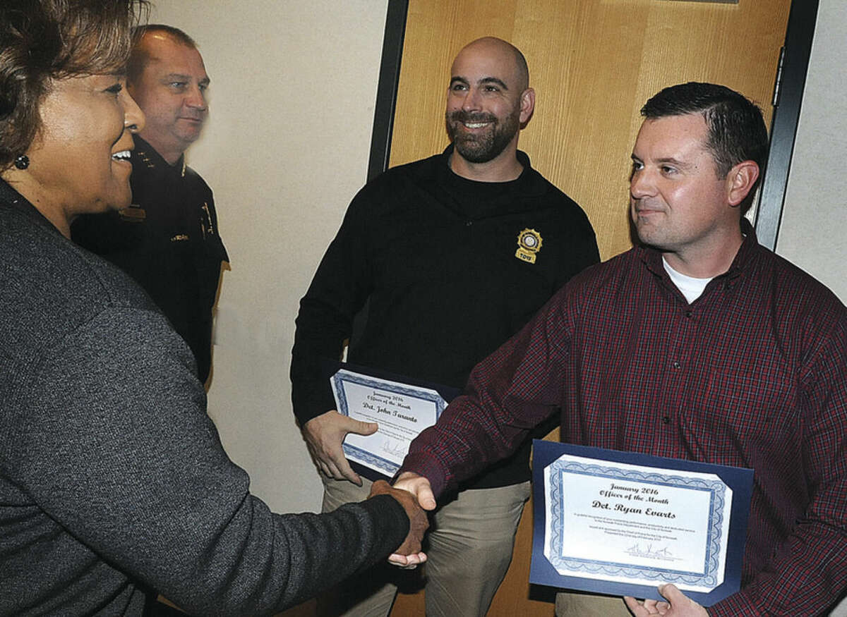 Hour photo/Matthew Vinci Officers of the month were honored Monday at the Norwalk Police Department. At left, Police Commissioner Fran Collier Clemmons shakes hands with Det. Ryan Evarts. Rear left, Police Chief Thomas E. Kulhawik watches along with other honoree Det. John Taranto.