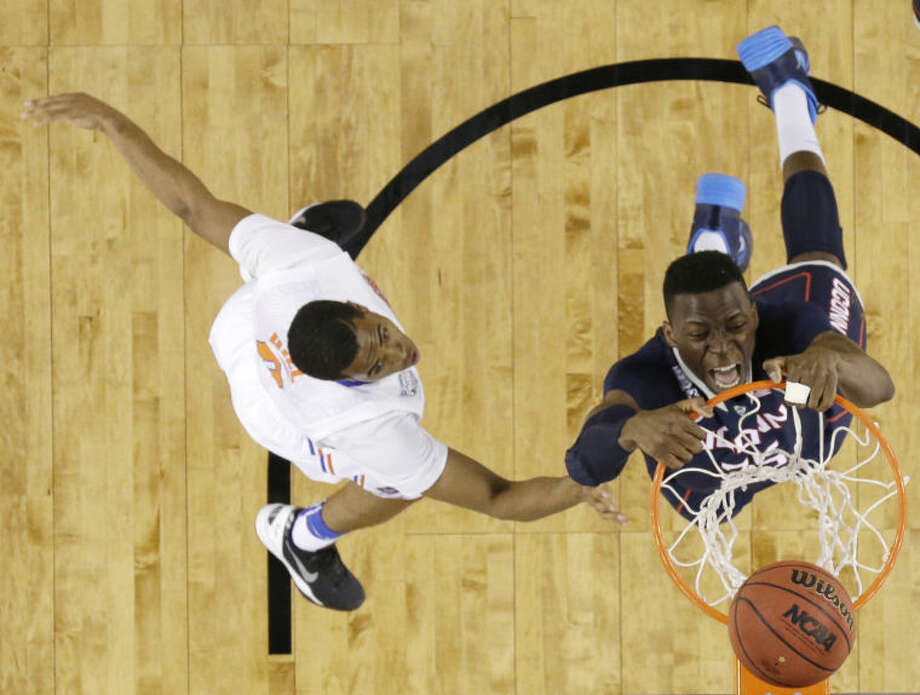 Connecticut center Amida Brimah, right, dunks the ball in front of Florida guard Kasey Hill during the second half of an NCAA Final Four tournament college basketball semifinal game Saturday, April 5, 2014, in Arlington, Texas. (AP Photo/David J. Phillip)