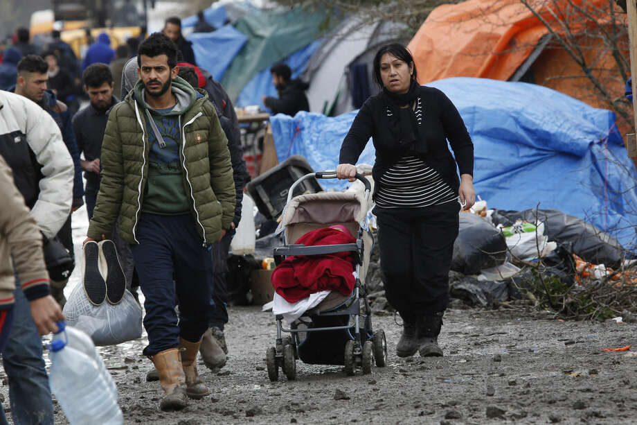 """A migrant family walk in the mud in a makeshift camp where over 1,000 migrants mostly from Iraqi Kurdistan live in Grand-Synthe, near the northern town of Dunkerque, France, Wednesday Feb. 24, 2016. The clock is ticking for hundreds of migrants in the nearby port city of Calais waiting for a judge to decide whether to postpone an eviction order in the camp locally referred to as """"the jungle"""". (AP Photo/Jerome Delay)"""
