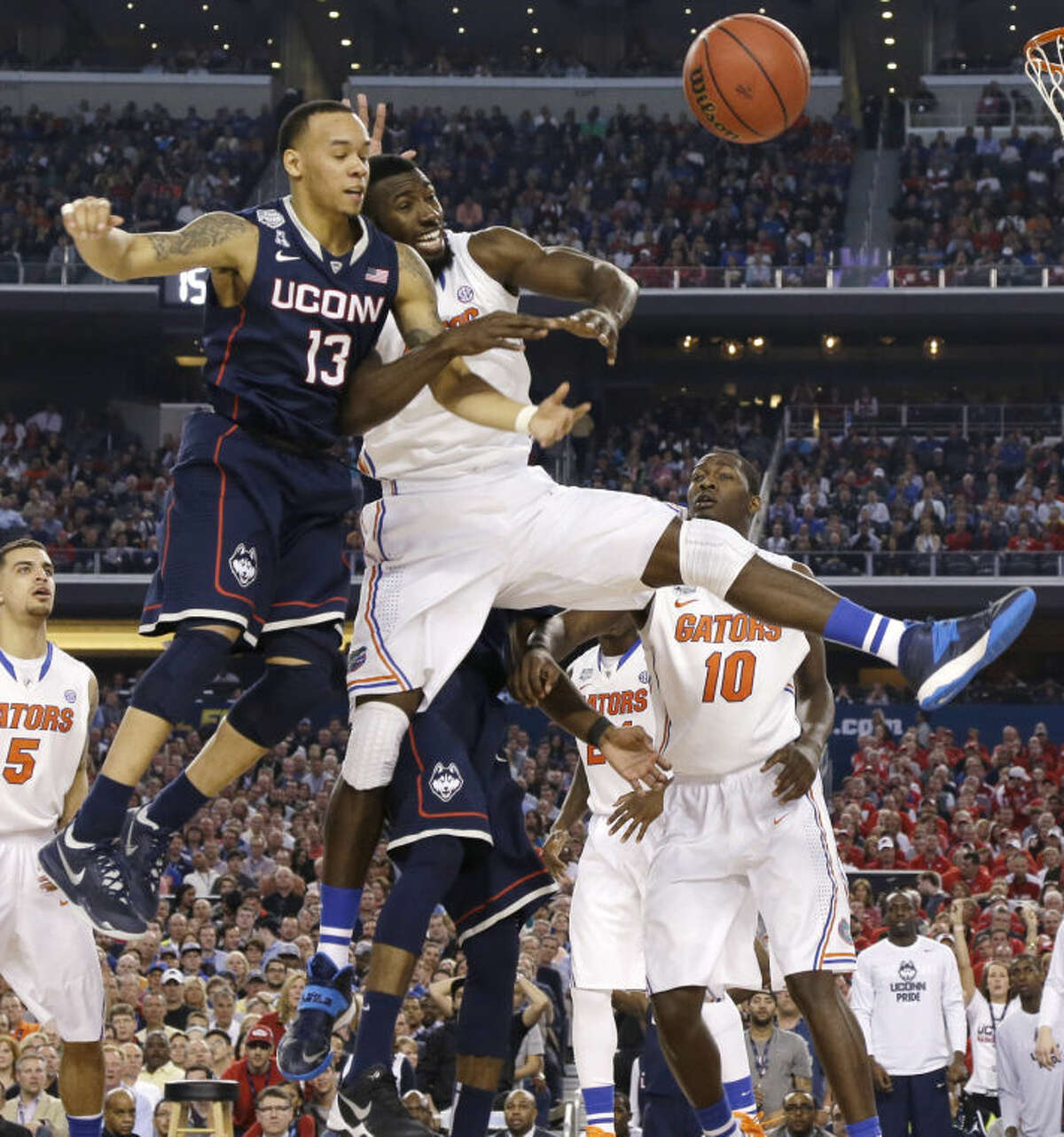 Connecticut guard Shabazz Napier, left, fights for a loose ball with Florida center Patric Young during the second half of an NCAA Final Four tournament college basketball semifinal game Saturday, April 5, 2014, in Arlington, Texas. (AP Photo/Eric Gay)