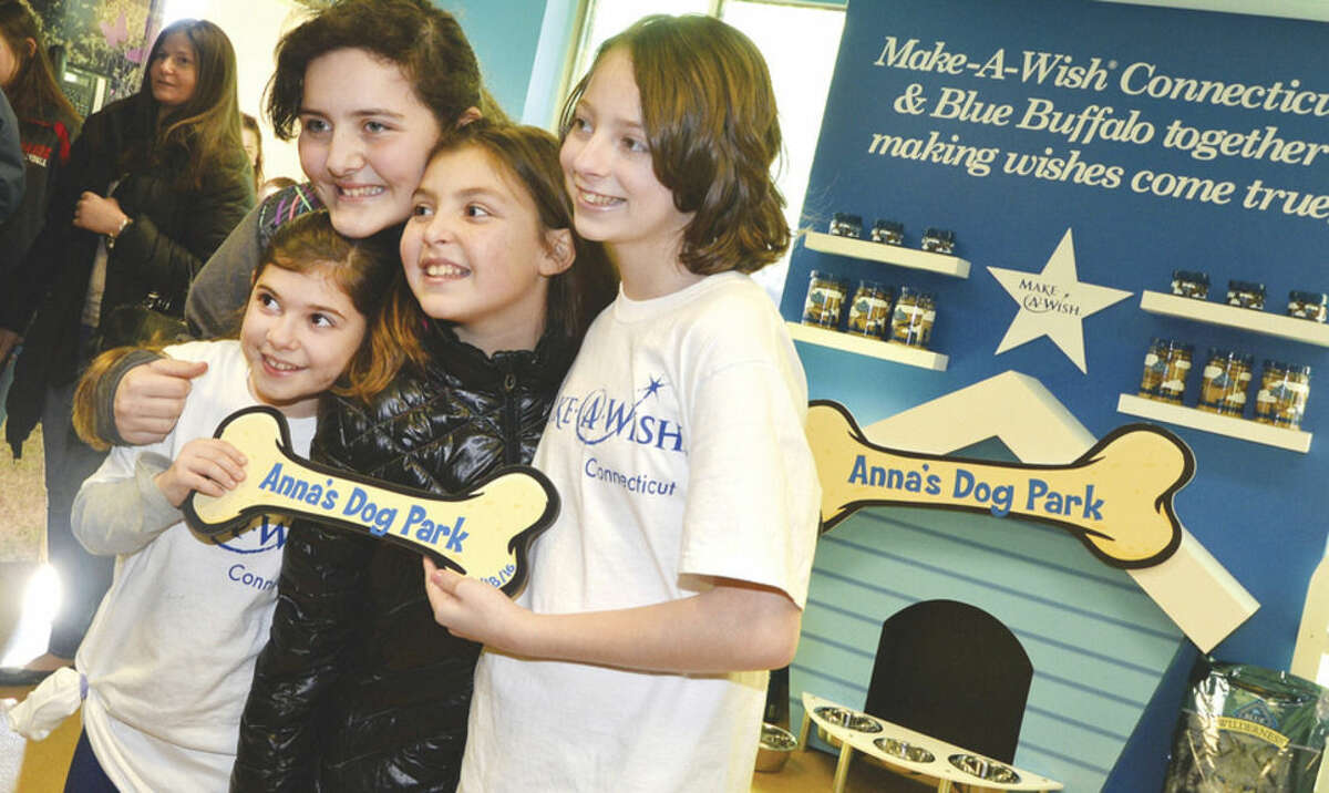 Hour Photo/Alex von Kleydorff 11 yr old Anna getner poses for a photo with her dog bone sign after the Dog Park at PAWS is opened in her name