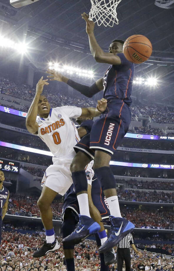 Florida guard Kasey Hill, left, passes around Connecticut center Amida Brimah during the second half of an NCAA Final Four tournament college basketball semifinal game Saturday, April 5, 2014, in Arlington, Texas. (AP Photo/David J. Phillip)