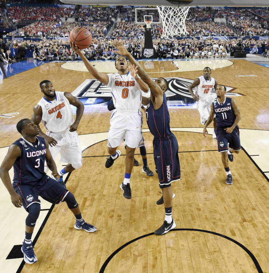 Florida guard Kasey Hill (0) shoots as Connecticut forward Phillip Nolan (0) defends during the second half of the NCAA Final Four tournament college basketball semifinal game Saturday, April 5, 2014, in Arlington, Texas. (AP Photo/Chris Steppig, pool)