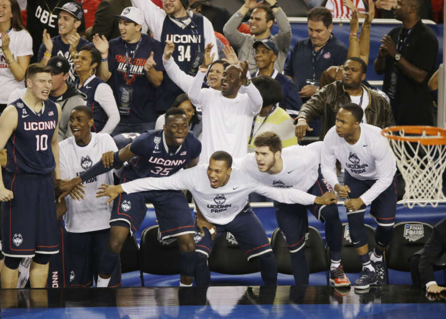 Connecticut celebrates in the final moments of their NCAA Final Four tournament college basketball semifinal game against Florida Saturday, April 5, 2014, in Arlington, Texas. Connecticut won 63-53. (AP Photo/Tony Gutierrez)