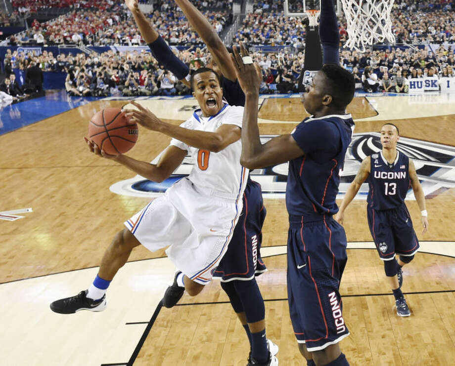 Florida guard Kasey Hill is defended by Connecticut center Amida Brimah during the second half of the NCAA Final Four tournament college basketball semifinal game Saturday, April 5, 2014, in Arlington, Texas. (AP Photo/Chris Steppig, pool)