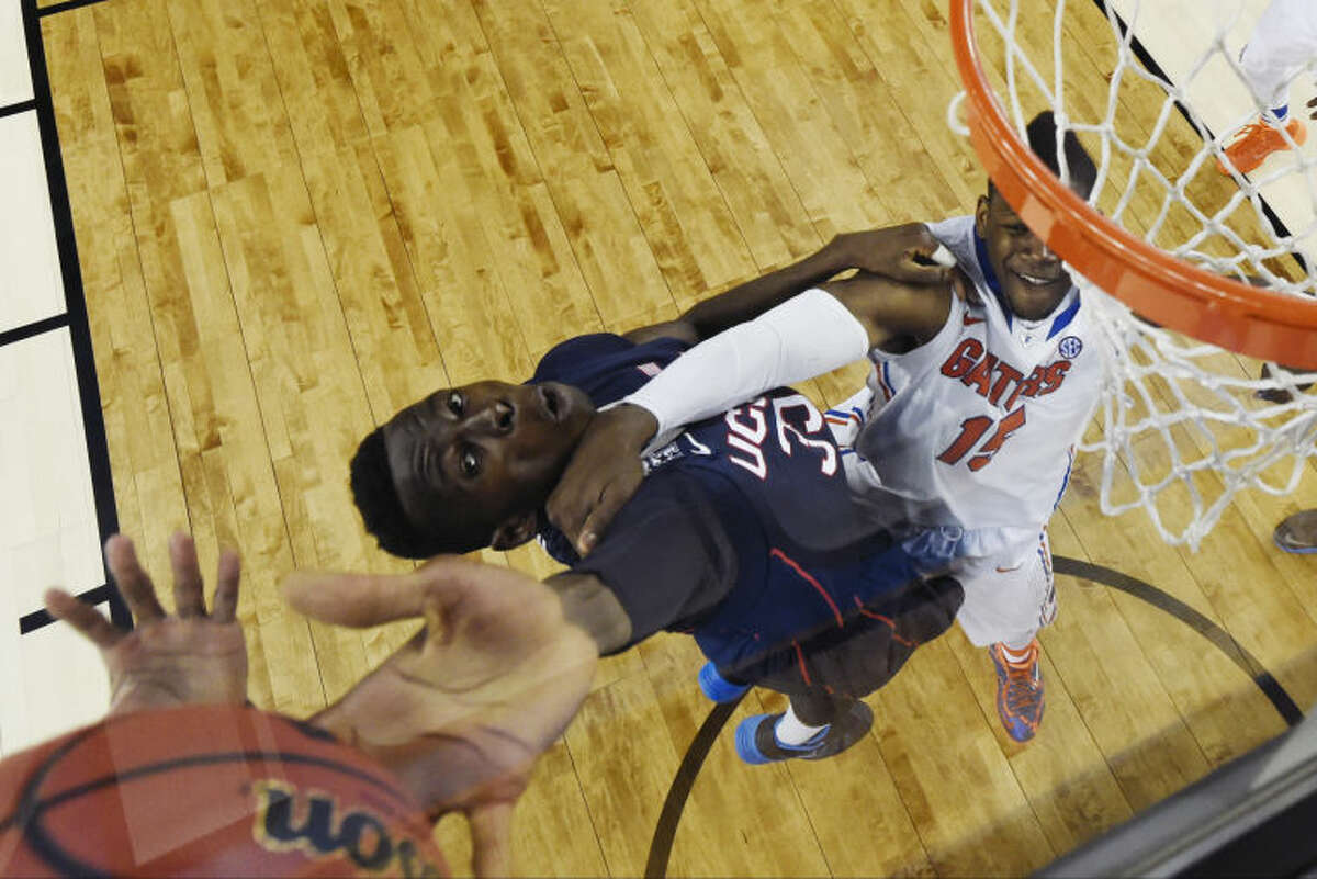 Connecticut center Amida Brimah (35) reaches for the ball as Florida forward Will Yeguete (15) defends during the second half of the NCAA Final Four tournament college basketball semifinal game Saturday, April 5, 2014, in Arlington, Texas. (AP Photo/Chris Steppig, pool)