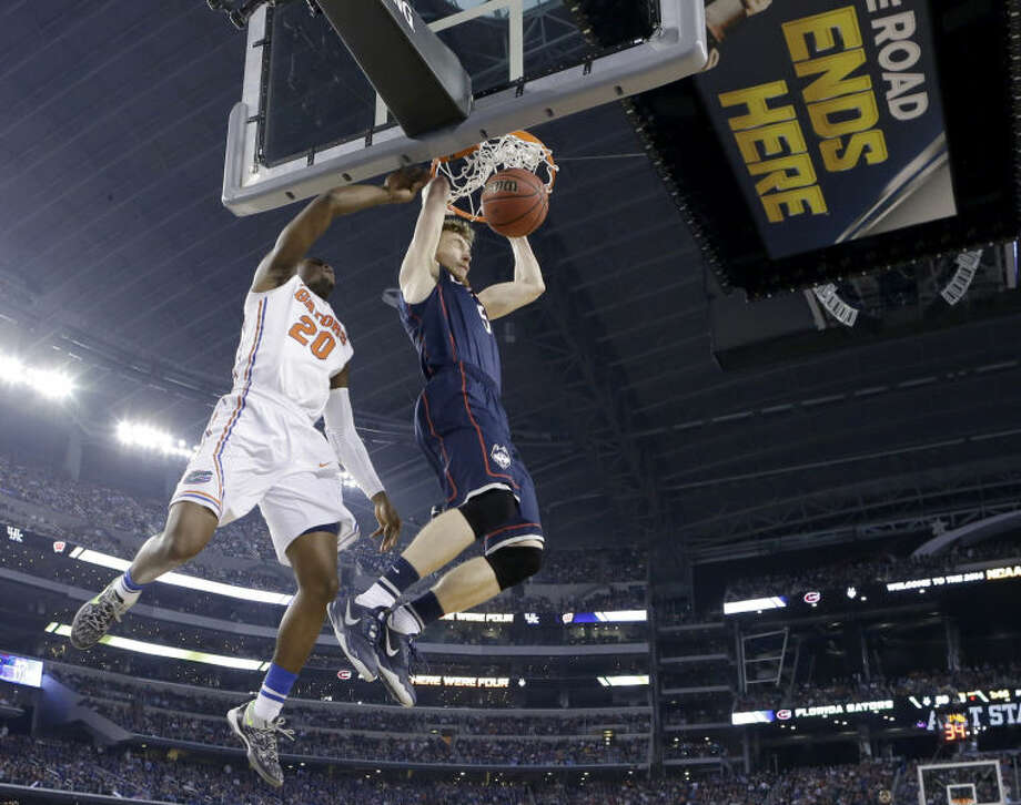 Connecticut guard/forward Niels Giffey (5) dunks as Florida guard Michael Frazier II (20) defends during the second half of the NCAA Final Four tournament college basketball semifinal game Saturday, April 5, 2014, in Arlington, Texas. Connecticut won 63-53. (AP Photo/Eric Gay)