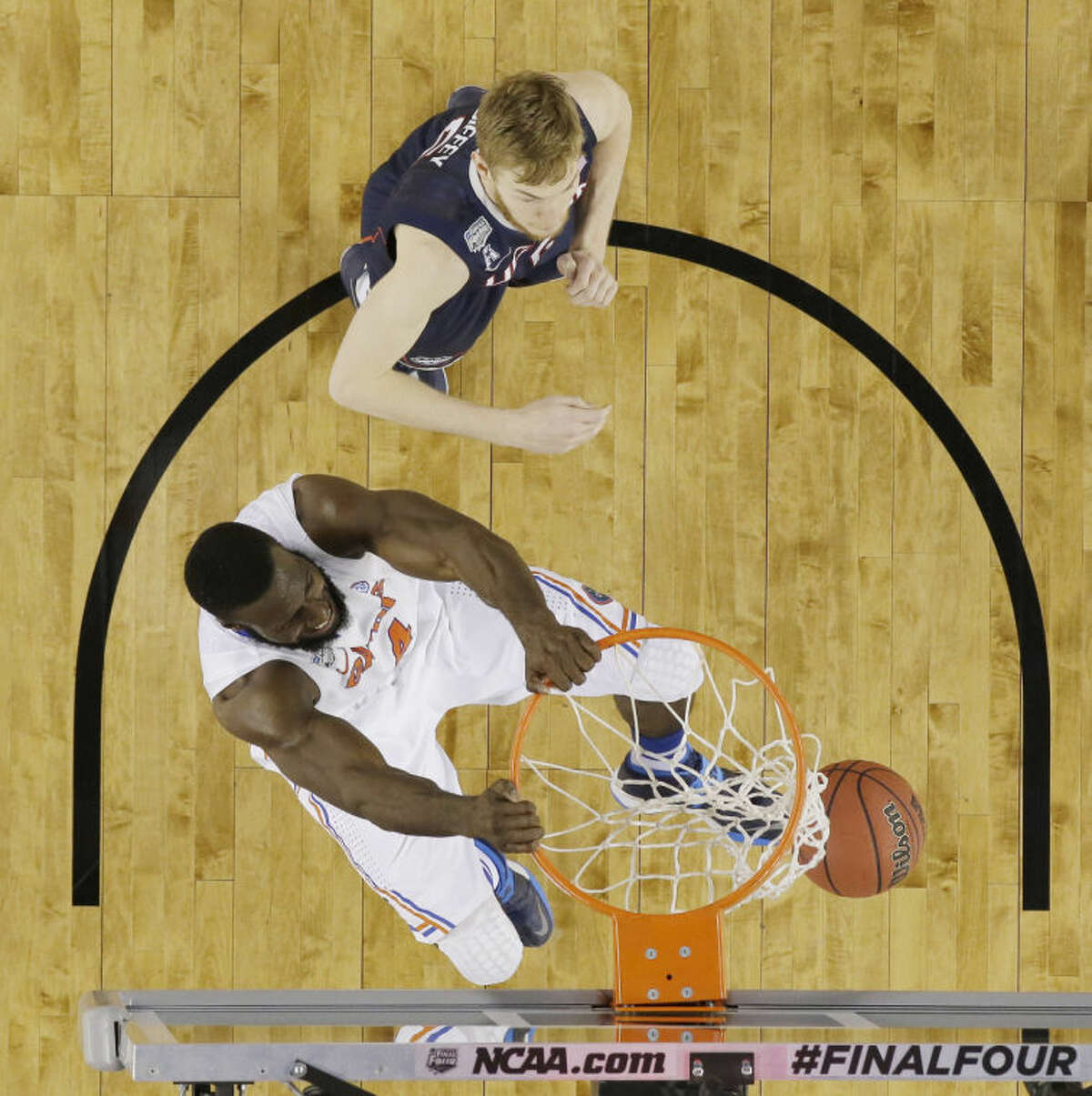 Florida center Patric Young (4) dunks as Connecticut guard/forward Niels Giffey (5) looks on during the second half of the NCAA Final Four tournament college basketball semifinal game Saturday, April 5, 2014, in Arlington, Texas. (AP Photo/David J. Phillip)