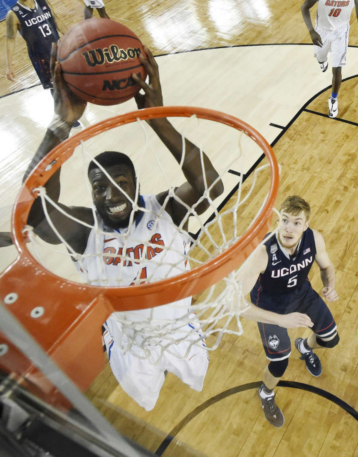 Florida center Patric Young (4) dunks as Connecticut guard/forward Niels Giffey (5) looks on during the second half of the NCAA Final Four tournament college basketball semifinal game Saturday, April 5, 2014, in Arlington, Texas. (AP Photo/Chris Steppig, pool)