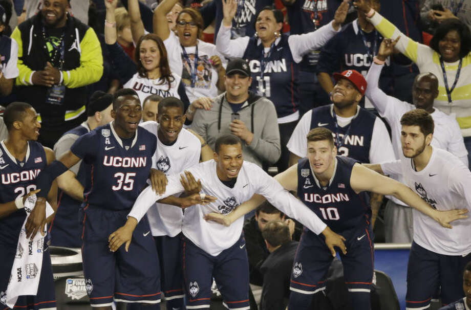 Connecticut players and fans begin to celebrate in the final moments of the team's 63-53 victory over Florida at their NCAA Final Four tournament college basketball semifinal game Saturday, April 5, 2014, in Arlington, Texas. (AP Photo/Tony Gutierrez)