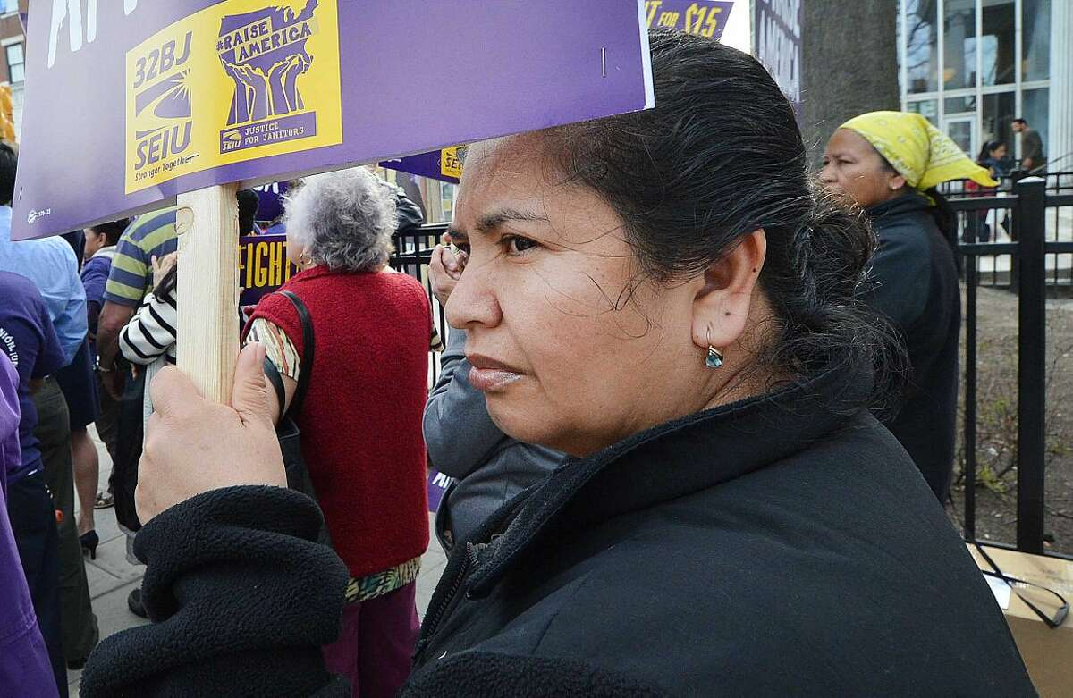 Hour Photo/Alex von Kleydorff Olivi Lorenza listens to speakers in downtown Stamford to rally for higher wages and to echo the global wave of protests against wage inequality that has been called the 'Fight for $15'. Members of 32BJ Union in Stamford march as workers across the country mobilize against income inequality.