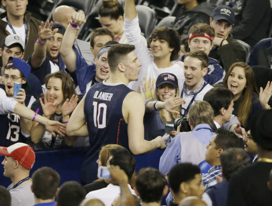 Connecticut fans celebrate with forward Tyler Olander after their team beat Florida 63-53 at their NCAA Final Four tournament college basketball semifinal game Saturday, April 5, 2014, in Arlington, Texas. (AP Photo/Tony Gutierrez)