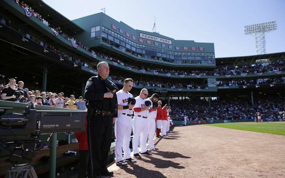 Boston Red Sox players, fans and a Boston Police officer pause for a moment of silence at 2:49pm, the time of the first bomb explosion near the finish line of the Boston Marathon in 2013, at the start of the fourth inning of a baseball game against the Washington Nationals at Fenway Park in Boston, Wednesday, April 15, 2015. Boston marked the second anniversary of the bombings with a subdued remembrance that includes a moment of silence, the pealing of church bells and a call for kindness. (AP Photo/Charles Krupa)