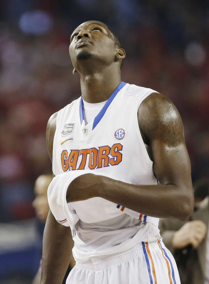 Florida forward Dorian Finney-Smith checks the scoreboard in the final moments against Connecticut at their NCAA Final Four tournament college basketball semifinal game Saturday, April 5, 2014, in Arlington, Texas. Connecticut won 63-53. (AP Photo/David J. Phillip)