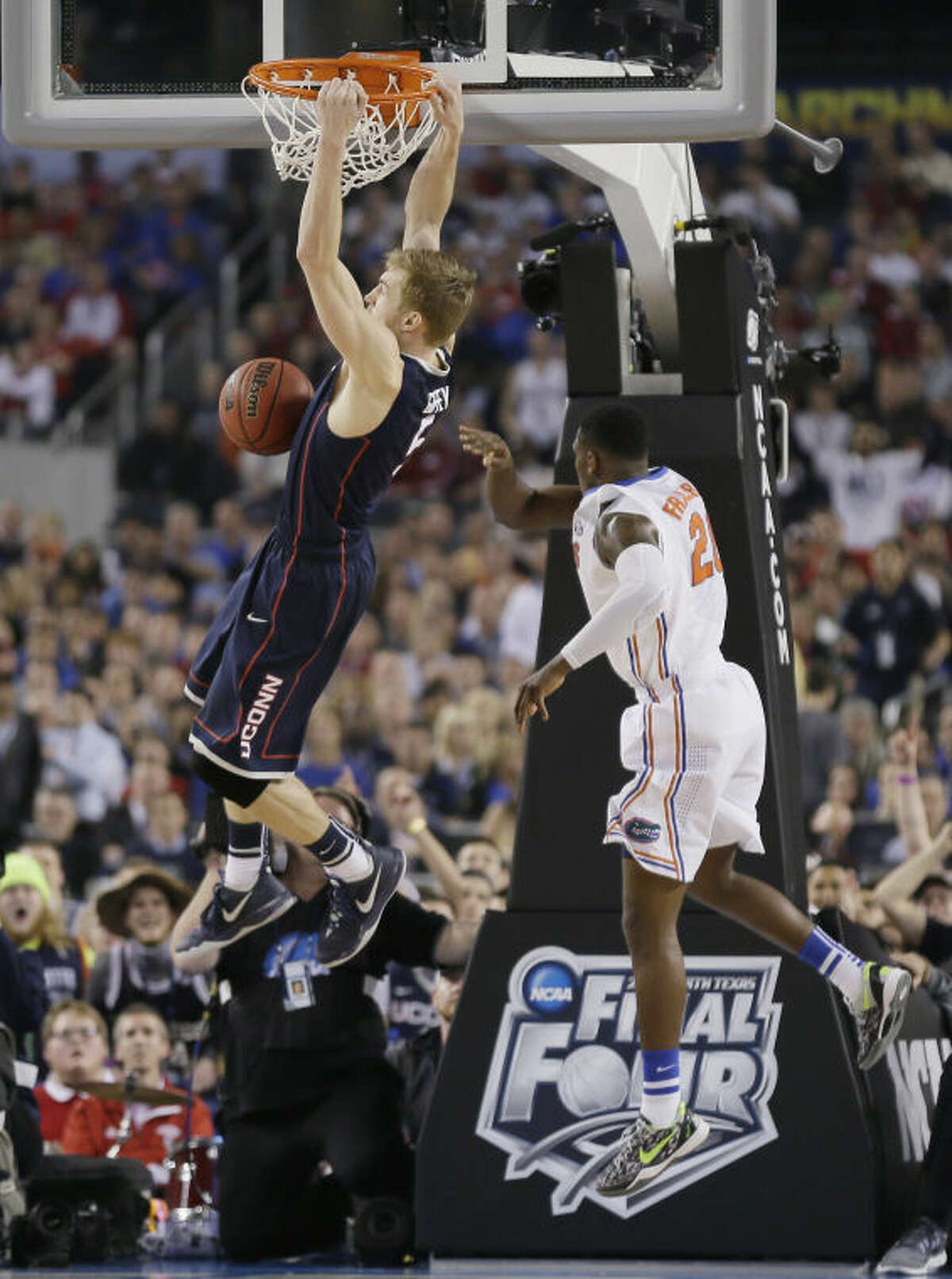 Connecticut forward Niels Giffey, left, dunks the ball in front of Florida guard Michael Frazier II during the second half of an NCAA Final Four tournament college basketball semifinal game Saturday, April 5, 2014, in Arlington, Texas. Connecticut won 63-53. (AP Photo/Charlie Neibergall)