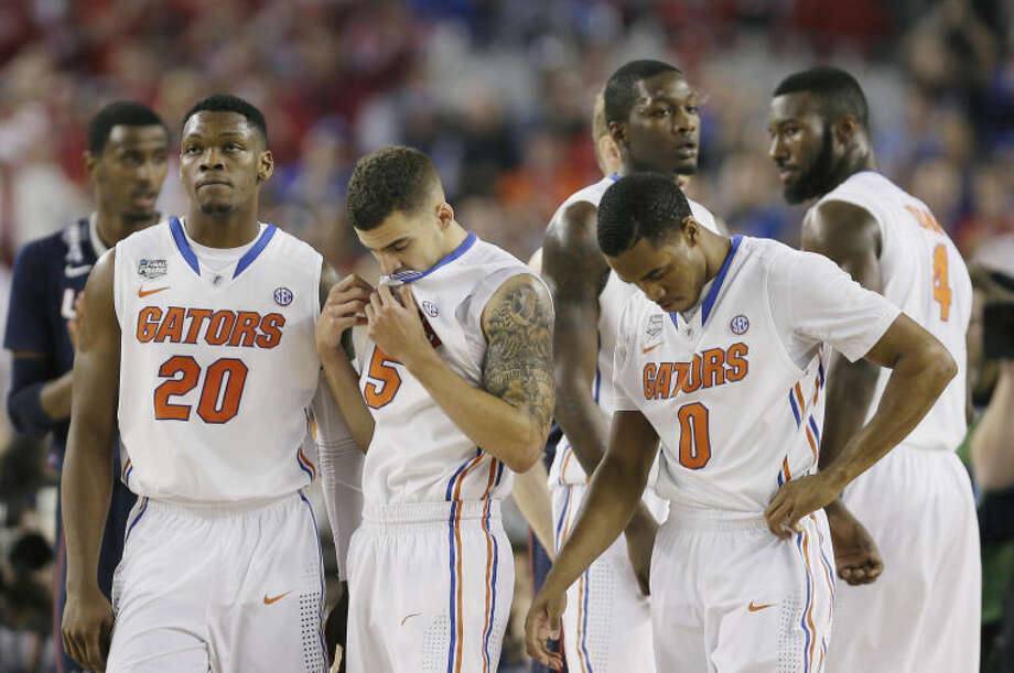 Florida players Michael Frazier II (20), Scottie Wilbekin (5), Kasey Hill (0) react in the final moments against Connecticut during their NCAA Final Four tournament college basketball semifinal game Saturday, April 5, 2014, in Arlington, Texas. Connecticut won 63-53. (AP Photo/Charlie Neibergall)