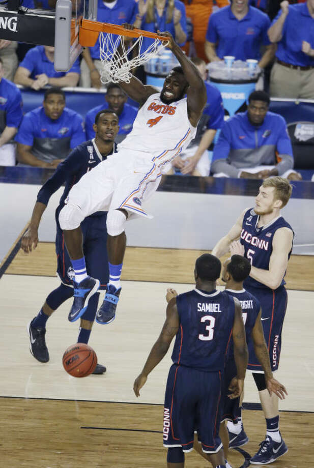 Florida center Patric Young (4) dunks the ball in front of Connecticut guard Terrence Samuel (3) during the second half of an NCAA Final Four tournament college basketball semifinal game Saturday, April 5, 2014, in Arlington, Texas. (AP Photo/Tony Gutierrez)