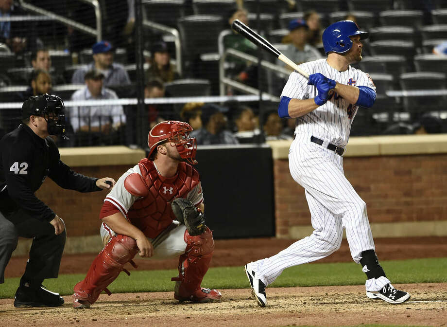 New York Mets first baseman Lucas Duda hits an RBI double in front of Philadelphia Phillies catcher Cameron Rupp in the sixth inning of a baseball game at Citi Field on Wednesday, April 15, 2015, in New York. (AP Photo/Kathy Kmonicek)