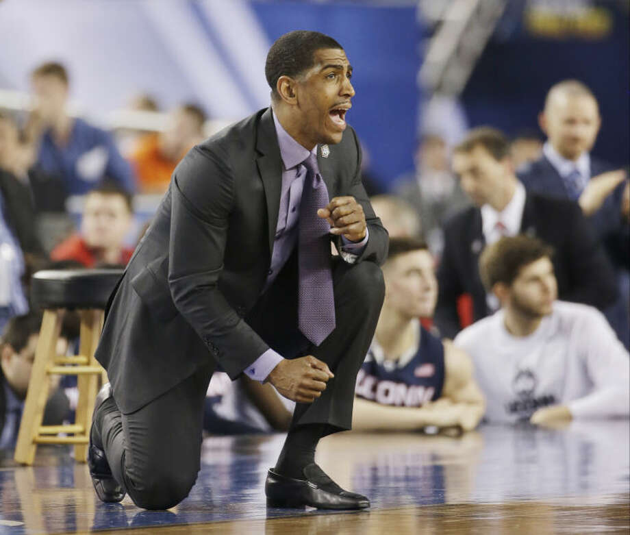 Connecticut head coach Kevin Ollie cheers his team against Florida during the second half of the NCAA Final Four tournament college basketball semifinal game Saturday, April 5, 2014, in Arlington, Texas. Connecticut won 63-53. (AP Photo/David J. Phillip)